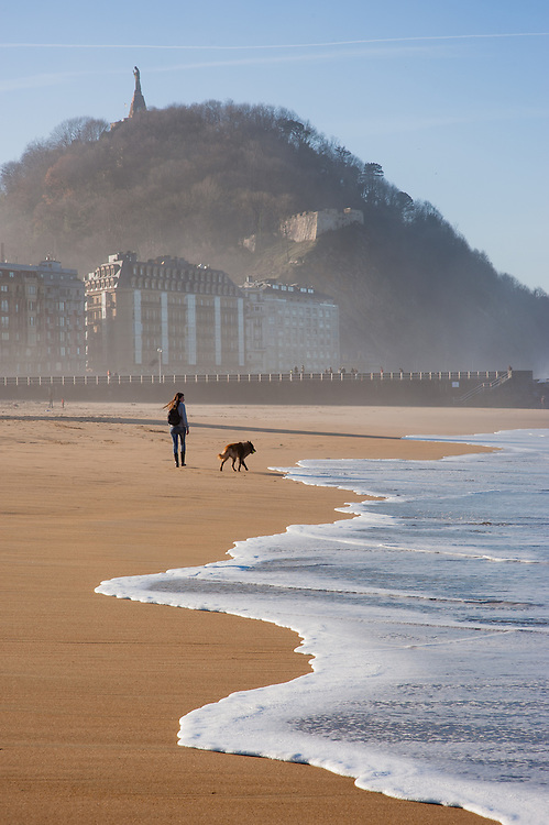 Woman and her dog walking on Zurriola beach in San Sebastian (Spain)