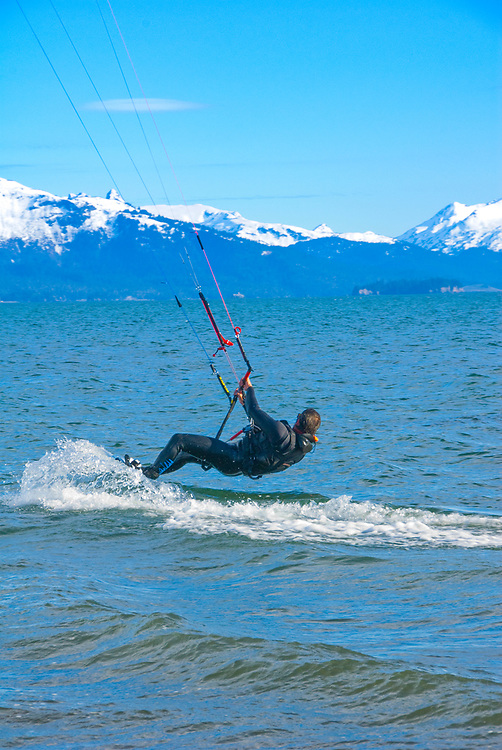 Trace Carlos dashes across waves of Kachemak Bay in Homer, Alaska surrounded by the Kenai Mts. MR