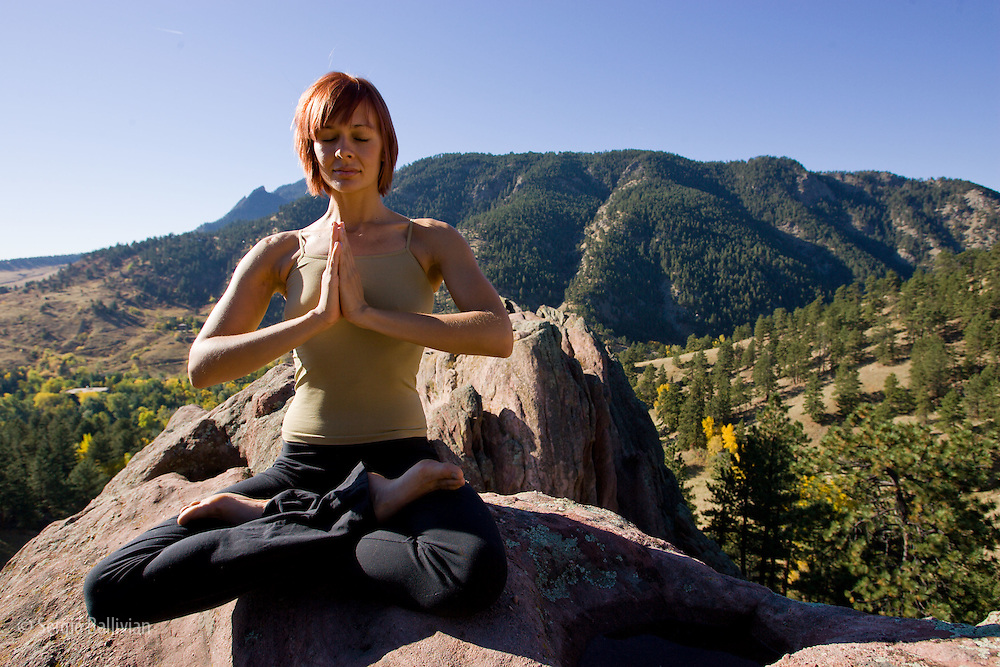 A yonug woman doing yoga at Red Rocks park in Boulder, Colorado during autumn.