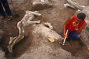 Having just unearthed more bodies from layers of volcanic ash and pumice, an archaeologist's assistant pauses for a cigarette, kneeling beside a victim of the AD79 eruption of Mount Versuvius over the ancient Roman town of Pompeii. Buried beneath huge amounts of toxic material this person was suffocated and crushed from falling debris. Preserved in a shell of volcanic material it is to be removed from this site on top of a villa roof where, it is calculated, this citizen was one of the last to die, having climbed 4 metres above ground level to await its fate. The Italian man ears a red t-shirt and holds a pick that has scraped and brushed away the soil to reveal the human form which also shows another body beneath. Others litter the rooftop too proving that many survivors of the first eruption perished after the second many hours later.