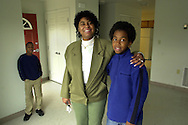 Lois Hinson, and her son Damier Belgrave, 11, left, are shown in their new home in Chatham Estates, Saturday, March 16 2002, in Chester, Pa. Hinson had lived in the old Chester housing projects two years ago, before they were torn down and replaced with new homes. On the left is Mikaun WWiggins, 10. Chatham Estates was built through the U.S. Department of Housing and Urban Development's HOPE VI program, which called for demolishing decrepit public-housing towers and replacing them with townhouses and houses.  (Photo by William Thomas Cain/photodx.com)