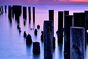 Old Naples Pier Pilings silhouetted against sunset in Naples Florida