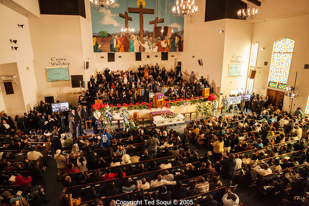 """People take cover as gangbangers shoot bullets into the air at the Funeral services for Stanley """"Tookie"""" Williams at Bethel A.M.E. Church in S. Central LA. About 2000 people attended the services which included many gang members. The funeral was a star studded event attended by Jesse Jackson and rapper-actor Snoop Dogg, Nation of Islam leader Louis Farrakhan, and Bianca Jagger.  Loudspeakers and a large TV screen brought the service to many of the onlookers who could not get inside the packed church."""