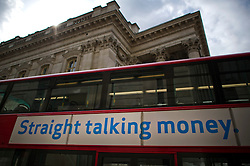 "© London News Pictures. 01/07/2013. London, UK. A bus carrying a money lending advert reading ""Straight Talking MOney"" passes in front of the Royal Exchange in central London on July 01, 2013. The Bank of England is due to release the Money and Credit report for May. Photo credit: Ben Cawthra/LNP"
