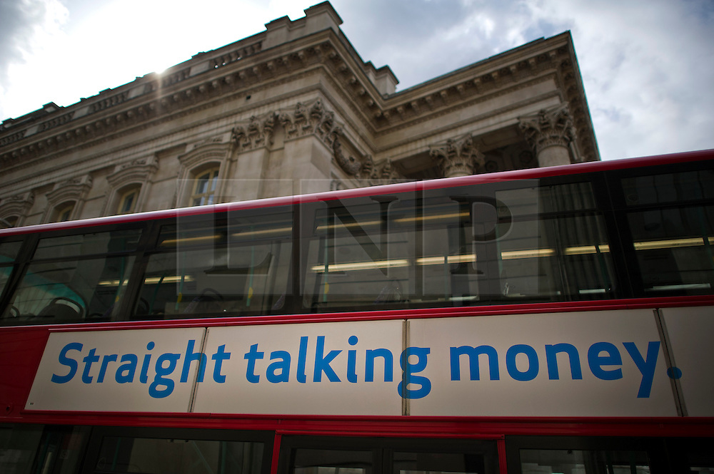"""© London News Pictures. 01/07/2013. London, UK. A bus carrying a money lending advert reading """"Straight Talking MOney"""" passes in front of the Royal Exchange in central London on July 01, 2013. The Bank of England is due to release the Money and Credit report for May. Photo credit: Ben Cawthra/LNP"""