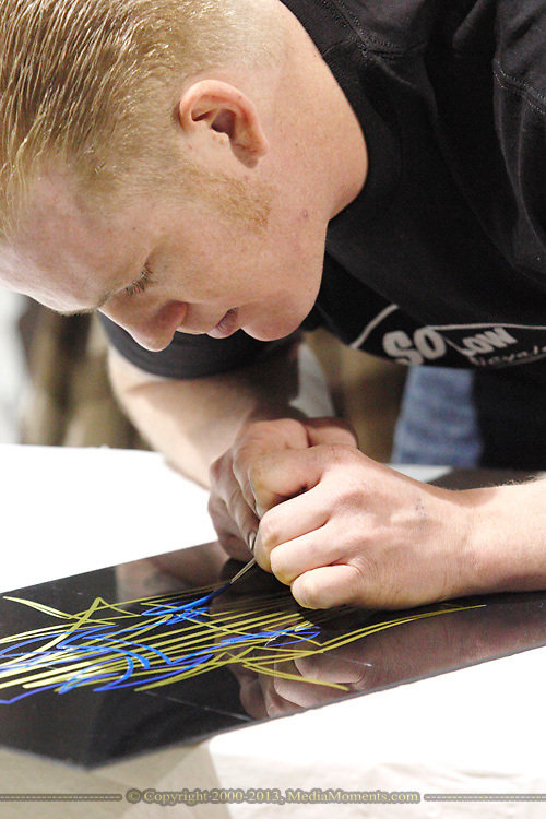 Jake McMahan of New Carlisle works on a pinstripe panel to be auctioned off during the KOI Hot Rod Fest Dayton at the Dayton Airport Expo Center in Vandalia, Sunday, March 12, 2012.
