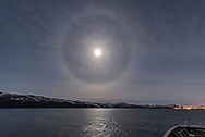 A halo around the nearly Full Moon (two days past full) over the Barent's Sea in northern Norway at a latitude of 71° North on November 5, 2017 from the cruise/ferry ship m/s Nordlys. The Moon is in Taurus — Orion is rising at left, Auriga is at top, with Gemini to the right.
