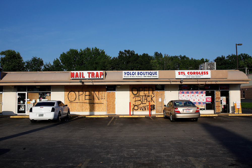 Boarded windows are a common sight in Ferguson. Plywood lined businesses are seen at a strip mall on West Florissant Ave.