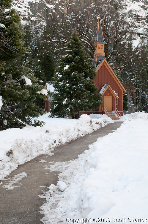 The shoveled sidewalk leads to the Yosemite Valley Chapel in Yosemite National Park.