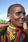 Africa, Tanzania, Female member of the Datooga tribe in traditional dress, beads and earrings. Beauty scarring can be seen around the eyes