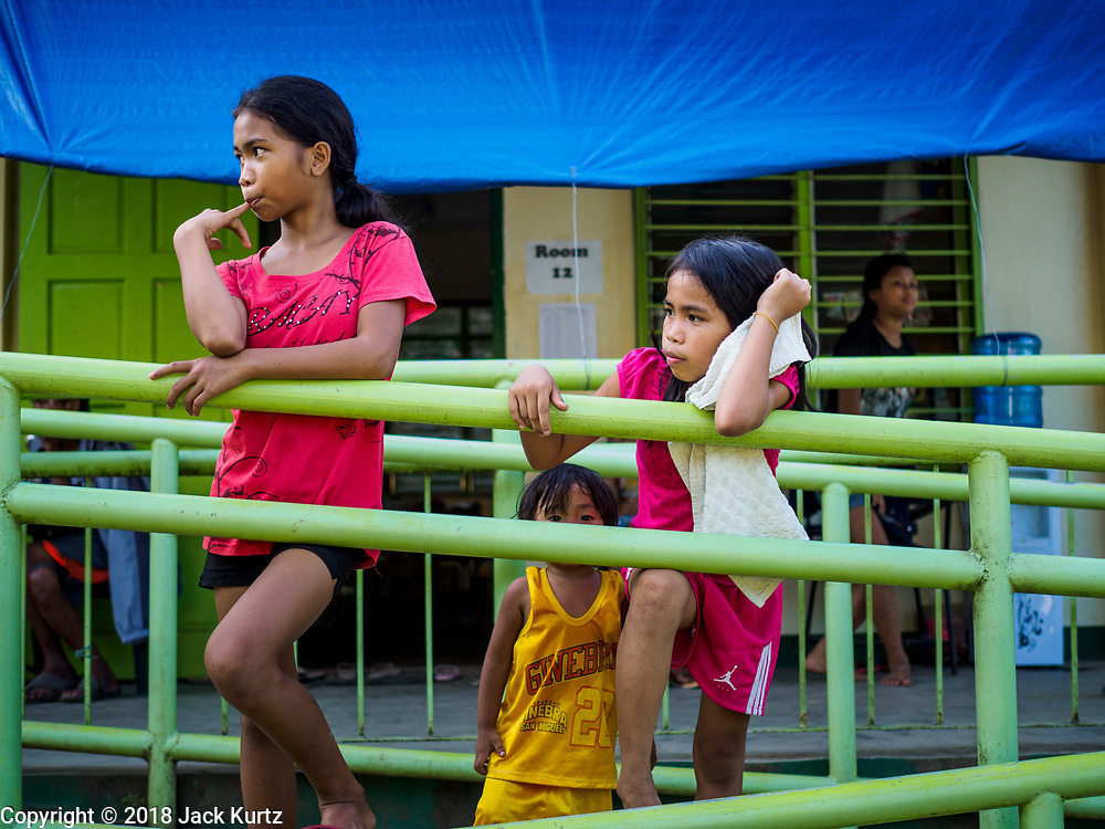 "22 JANUARY 2018 - CAMALIG, ALBAY, PHILIPPINES: Evacuees from the eruption of the Mayon volcano at Bariw National High School, the evacuation center they've been assigned to. There were a series of eruptions on the Mayon volcano near Legazpi Monday. The eruptions started Sunday night and continued through the day. At about midday the volcano sent a plume of ash and smoke towering over Camalig, the largest municipality near the volcano. The Philippine Institute of Volcanology and Seismology (PHIVOLCS) extended the six kilometer danger zone to eight kilometers and raised the alert level from three to four. This is the first time the alert level has been at four since 2009. A level four alert means a ""Hazardous Eruption is Imminent"" and there is ""intense unrest"" in the volcano. The Mayon volcano is the most active volcano in the Philippines. Sunday and Monday's eruptions caused ash falls in several communities but there were no known injuries.    PHOTO BY JACK KURTZ"