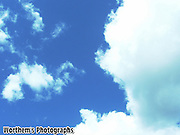 A sunny day with a white puffy cloud.