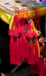 Bright red tassels, souvenir shop on West Street, Yangshou.  Yangshuo is a county and city under the jurisdiction of Guilin City, in the northeast of Guangxi Province, China. Its seat is located in Yangshuo Town. Surrounded by karst peaks and bordered on one side by the Li River it is easily accessible by bus or by boat from nearby Guilin. It is a major tourist and resort destination for Chinese and foreigners alike, and West Street has been a  major shopping street for some 1400 years.