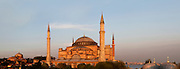 Panoramic view of Hagia Sophia, 532-37, by Isidore of Miletus and Anthemius of Tralles, Istanbul, Turkey, at sunset. Hagia Sophia, The Church of the Holy Wisdom, has been a  Byzantine church and an Ottoman mosque and is now a museum. The current building, the third on the site, commissioned by Emperor Justinian I, is a very fine example of Byzantine architecture. The historical areas of the city were declared a UNESCO World Heritage Site in 1985. Picture by Manuel Cohen.