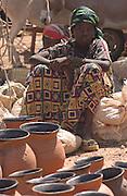 Teenage girl selling pottery at weekly market in Gorom Gorom, Northeastern Burkina Faso, West Africa.