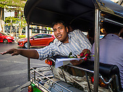"14 FEBRUARY 2015 - BANGKOK, THAILAND: Student activist Siriwit Serithiwat waves after he was detained and taken away by police in a tuk-tuk (three wheeled taxi) during a protest the military coup. Martial law is still in effect in Thailand and protests against the coup are illegal. Dozens of people gathered in front of the Bangkok Art and Culture Centre in Bangkok Saturday to hand out red roses and copies of George Orwell's ""1984."" Protestors said they didn't support either Red Shirts or Yellow Shirts but wanted a return of democracy in Thailand. The protest was the largest protest since June 2014, against the military government of General Prayuth Chan-Ocha, who staged the coup against the elected government. Police made several arrests Saturday afternoon but the protest was not violent.      PHOTO BY JACK KURTZ"