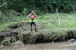 © Licensed to London News Pictures. 04/08/2019. Whaley Bridge, UK. Canal and Rivers Trust staff carry out a survey monitoring fast-flowing water , as an upstream river is diverted via a sluice in to a bywater that runs parallel to the reservoir . More rain is forecast overnight (Sunday 4th/Monday 5th August) in the town of Whaley Bridge in Derbyshire after earlier heavy rain caused damage to the Toddbrook Reservoir , threatening homes and businesses with flooding. Photo credit: Joel Goodman/LNP