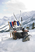 Skier resting in deckchair in mountains