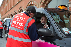 © licensed to London News Pictures. London, UK 23/11/2012. Workers of London Taxi Company, which makes black cabs, talking to cab drivers outside St Pancras Station in London as part of a campaign to save jobs after 156 workers lost their jobs. Photo credit: Tolga Akmen/LNP