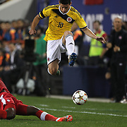 James Rodriguez, Colombia, jumps to avoid the challenge of Doneil Henry, Canada, during the Colombia Vs Canada friendly international football match at Red Bull Arena, Harrison, New Jersey. USA. 14th October 2014. Photo Tim Clayton