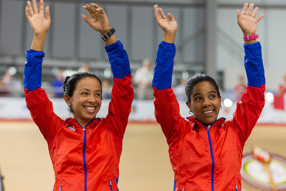 The Cuban team of Marlies Mejias (L)and  Lisandra Guerra celebrate their silver medal win in the women's team sprint final at the 2015 Pan American Games in Toronto, Canada, July 16,  2015.  AFP PHOTO/GEOFF ROBINS