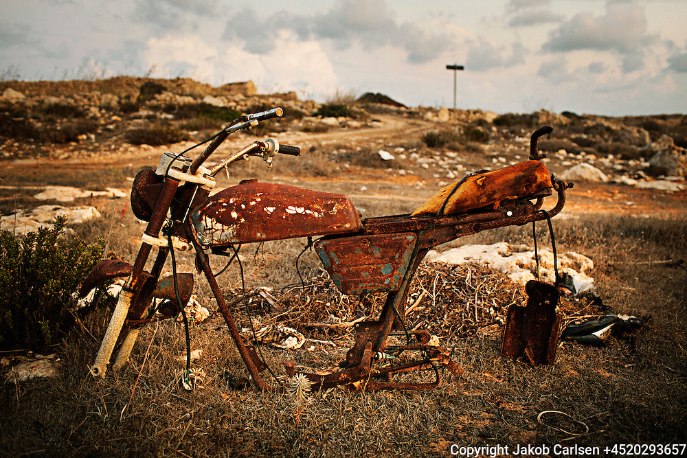 "Lampedusa is a small Italian island located in the Mediterranean Sea, east of Tunesia. Known as the prime transit point for illegal immigrants from Africa and its white sand beaches. The island has no sources of water other than irregular rainfall, and the landscape is dry and rocky. Along the coast and at ""The hill of shame"" the remnants of the immigrants belongings are scattered."