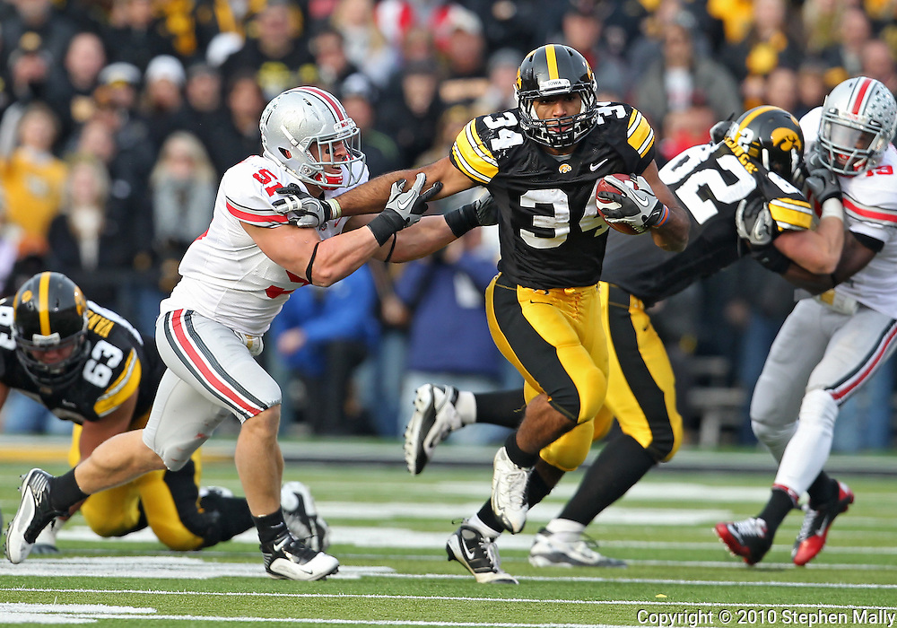 November 20 2010: Iowa Hawkeyes running back Marcus Coker (34) tries to pull away from Ohio State Buckeyes linebacker Ross Homan (51) during the first quarter of the NCAA football game between the Ohio State Buckeyes and the Iowa Hawkeyes at Kinnick Stadium in Iowa City, Iowa on Saturday November 20, 2010. Ohio State defeated Iowa 20-17.