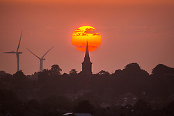 © Licensed to London News Pictures. 10/08/2020. Leeds UK. The sun rises this morning behind St Mary's church in the Garforth area of Leeds in Yorkshire as the Met Office issues a yellow warning for thunderstorms. Photo credit: Andrew McCaren/LNP