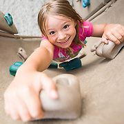 Young girl climbing  artificial rock climbing wall in playground. Model Release # ER20120624-00003