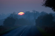 Winter sun sets over empty country road, Swinbrook, Oxfordshire,  UK