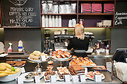 Back view of young woman working in bakery shop with pastries on display