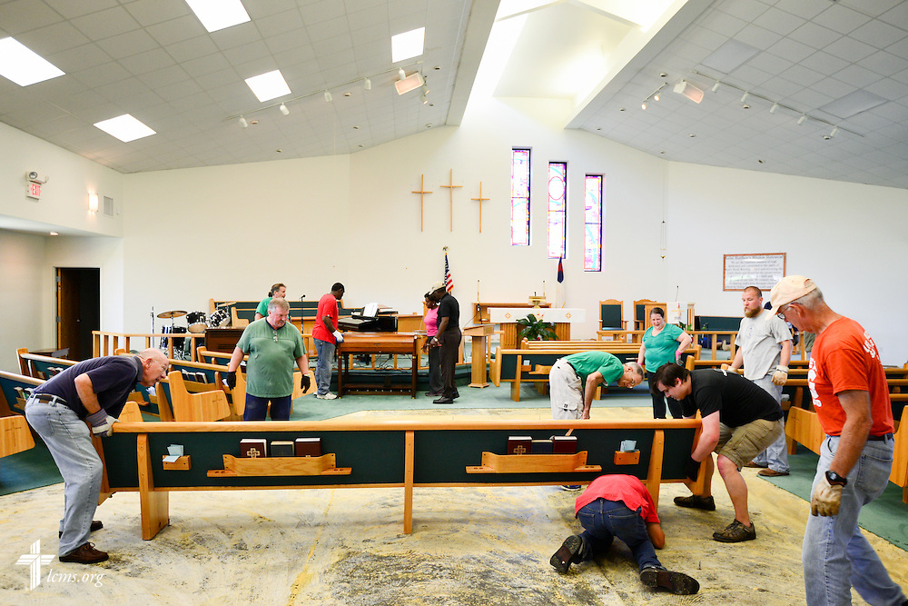 Volunteers remove the pews and carpet from the floodwater soaked carpet of St. Matthew Lutheran Church on Saturday, May 3, 2014, in Pensacola, Fla., Torrential rainfall led to widespread flooding in the area, damaging the fellowship hall and sanctuary of the church. LCMS Communications/Erik M. Lunsford