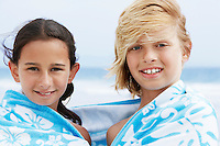 Pre-teen children wrapped in single towel on windy day