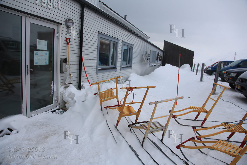 "Kicksleds, or ""sparks,"" sit outside mess hall at the international science village of Ny-Alesund on Spitsbergen island in Kongsfjorden; Svalbard, Norway."