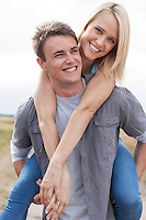 Happy young man giving piggyback ride to girlfriend on field