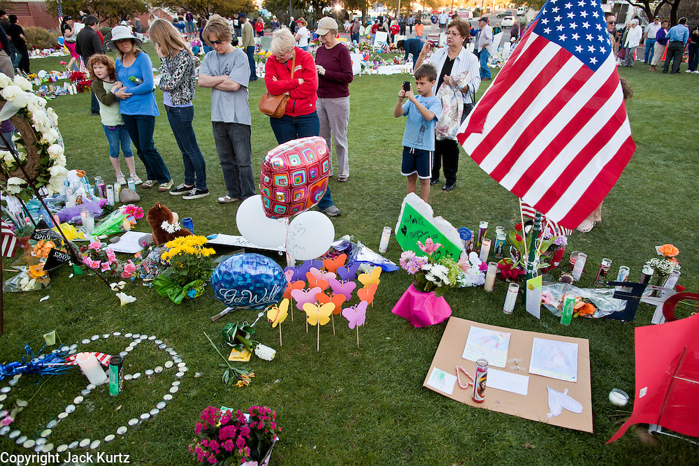"15 JANUARY 2011 - TUCSON, AZ: People visit the memorial on the lawn in front of the University Medical Center in Tucson, AZ, Saturday, January 15. The memorial has been growing since the mass shooting last week. Six people were killed and 14 injured in the shooting spree at a ""Congress on Your Corner"" event hosted by Congresswoman Gabrielle Giffords at a Safeway grocery store in north Tucson on January 8. Congresswoman Giffords, the intended target of the attack, was shot in the head and seriously injured in the attack. She is hospitalized at UMC. The alleged gunman, Jared Lee Loughner, was wrestled to the ground by bystanders when he stopped shooting to reload the Glock 19 semi-automatic pistol. Loughner is currently in federal custody at a medium security prison near Phoenix.  Photo by Jack Kurtz"
