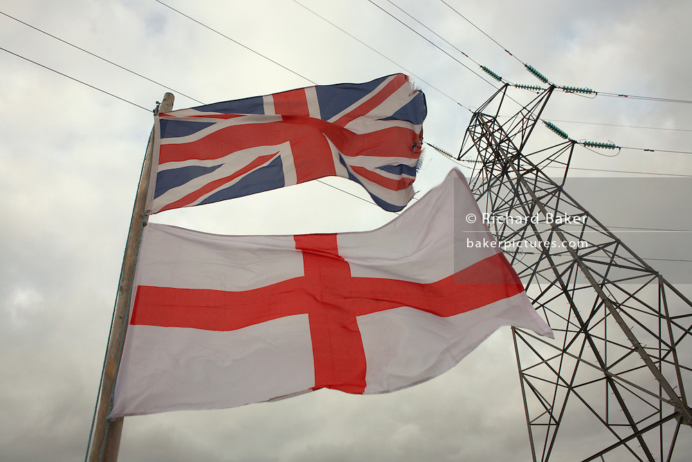 A Union Jack flag flies beneath the English Cross of St. George on a flag pole beneath an electricity pylon in a Somerset garden.
