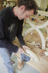 Man working on wooden chair leg during occupational therapy session in hospital workshop in preparation for returning to work,