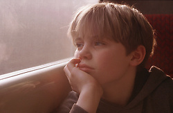 Young boy looking out of train window,