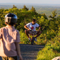 A teenage boy rides his young cousin's bike near the summit of Mount Agamenticus in York, Maine.