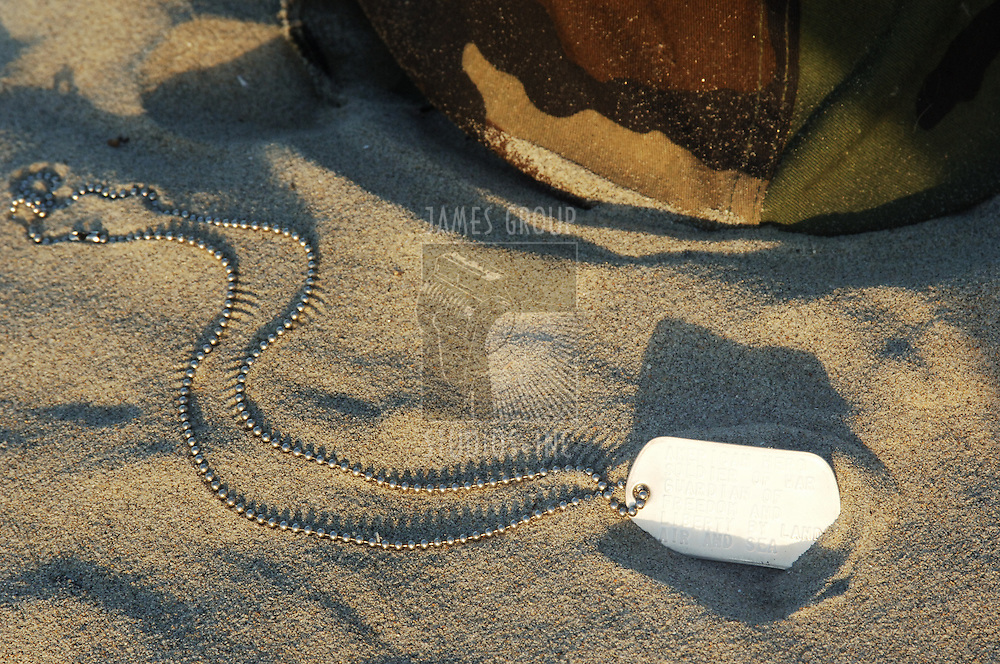 dog tag and helmet in sand