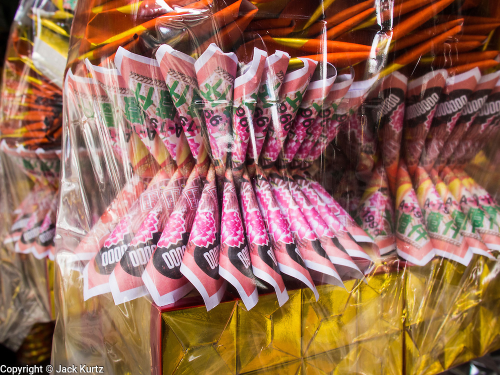 """26 AUGUST 2013 - BANGKOK, THAILAND: Ghost money for sale in Bangkok. The Chinese believe that burning """"ghost money"""" sends money to the spirits, advances their wealth in the next life and helps in improving luck in business or family. The seventh lunar month (August - September in 2013) is when the Chinese community believes that hell's gate will open to allow spirits to roam freely in the human world for a month. Many households and temples will hold prayer ceremonies throughout the month-long Hungry Ghost Festival (Phor Thor) to appease the spirits. During the festival, believers will also worship the Tai Su Yeah (King of Hades) in the form of paper effigies which will be """"sent back"""" to hell after the effigies are burnt.      PHOTO BY JACK KURTZ"""