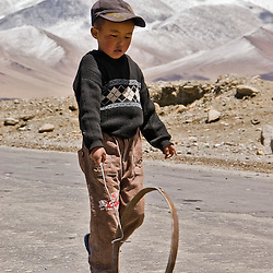 Boy playing with a wheel, Karakul lake, Pamir Highway, Tajikistan, Asia