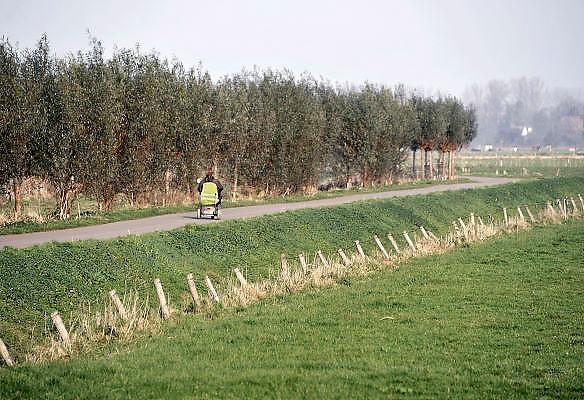 Nederland, Ubbergen, 20-11-2011Vrouw met lichamelijke beperking, handicap, rijdt in haar scootmobiel over een landweg.Foto: Flip Franssen/Hollandse Hoogte