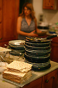 "An israeli family attending a ""Seder"",  the traditional passover dinner,  and reading the ""Hagada"" (the story of israeli's exodus from Egypt)  during the evening. A stack of dirty dishes after the meal"