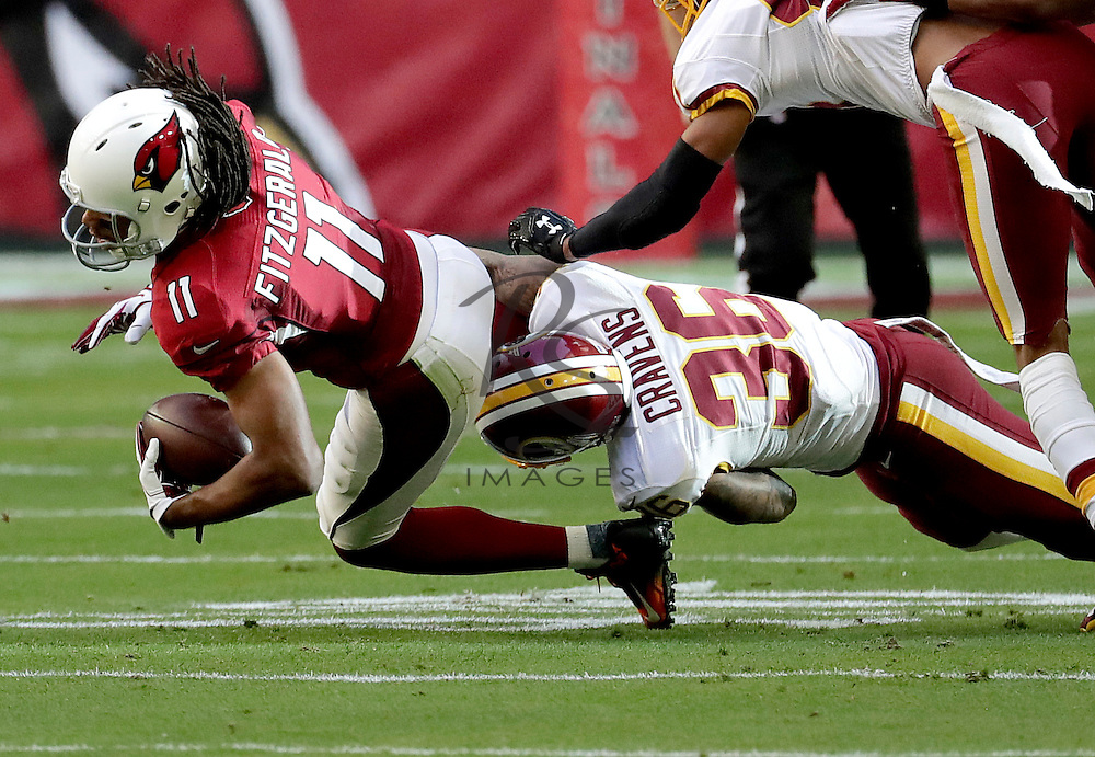 Arizona Cardinals wide receiver Larry Fitzgerald (11) is hit by Washington Redskins inside linebacker Su'a Cravens (36) during the first half of an NFL football game, Sunday, Dec. 4, 2016, in Glendale, Ariz. (AP Photo/Rick Scuteri)