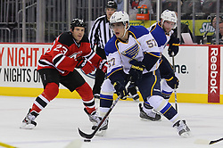 Feb 9; Newark, NJ, USA; St. Louis Blues left wing David Perron (57) skates with the puck while being chased by New Jersey Devils right wing David Clarkson (23) during the first period at the Prudential Center.