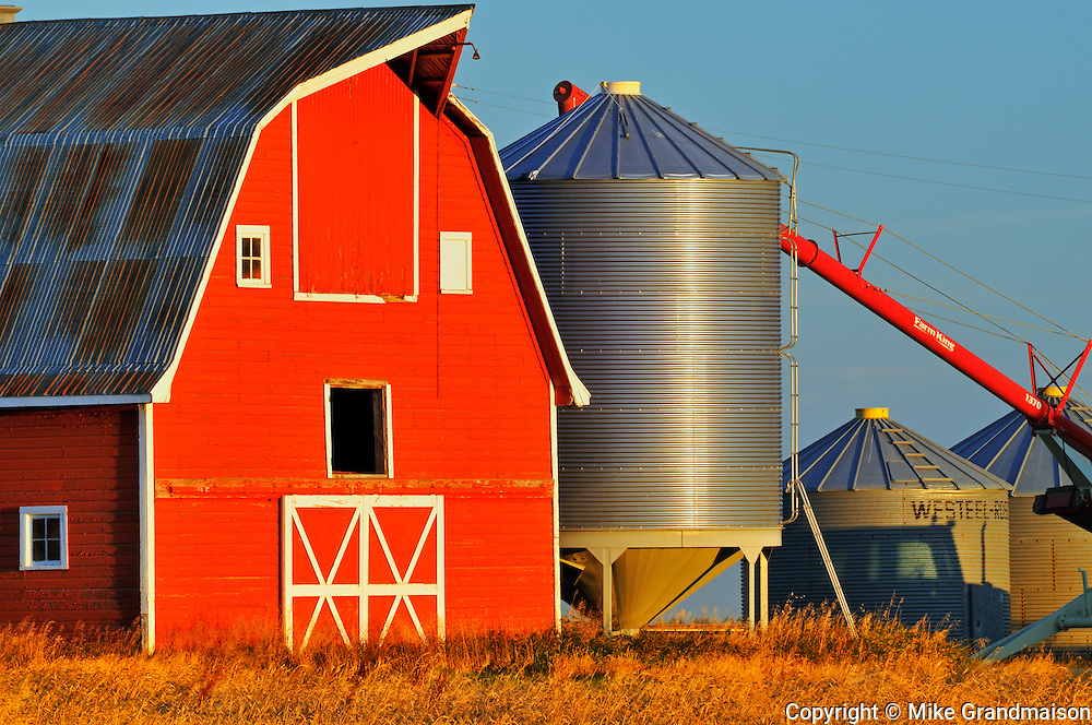Red barn, grain bins and auger at sunrise<br /> near Moose Jaw<br /> Saskatchewan<br /> Canada