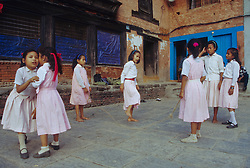 Asia, Nepal, Kathmandu, girls in school uniforms jumping rope in courtyard