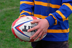 Boy holding rugby ball UK